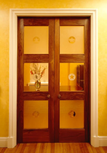 Bespoke pair of American black walnut doors with six glass panels and star motifs